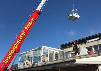 Inseldachdecker Kran hebt Material über Balkon